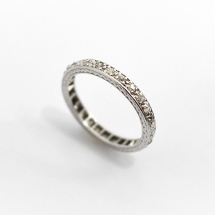 Platinum 1930's diamond full eternity ring. Comprising of old cut and eight cut diamonds, totalling approximately 0.75ct. Engraved decoration to channel settings. £1,400.00