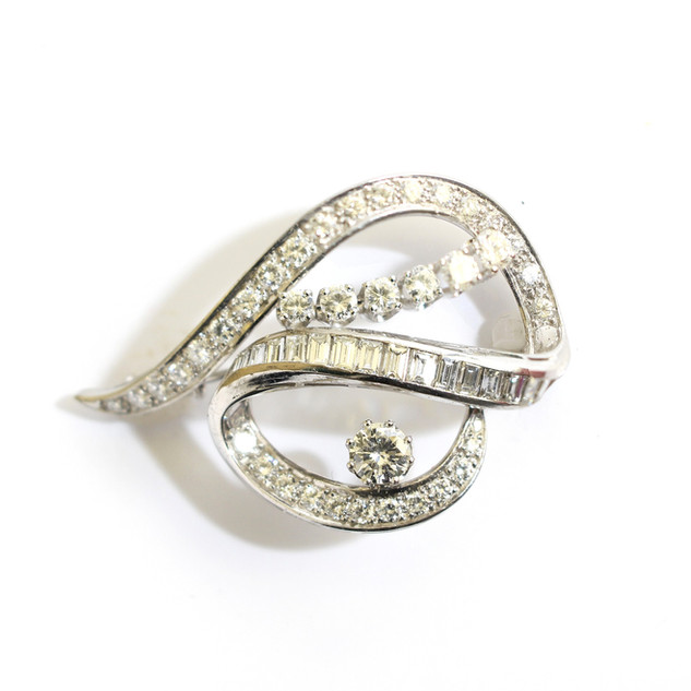 18ct white gold mounted diamond ribbon brooch. Comprising of a single circular modern brilliant cut diamond, approximately 0.50ct with straps of round diamonds and baguette cut diamonds. Total diamond weight estimated 3.80cts, G colour or better, Vs clarity. Circa 1960. In a Grey-Harris & Co fitted case. £4,750.00