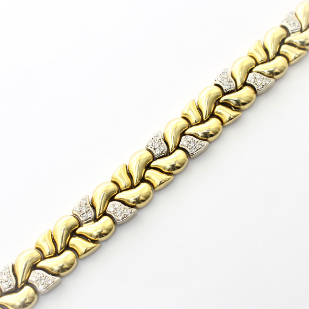 18ct yellow gold bracelet. Comprising of high polished domed links, partially set with circular diamonds. Total diamond weight estimated 2.15cts. Completed with invisable clasp. Circa 1980.