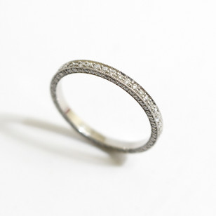 A platinum and diamond full eternity ring. The millegrain set brilliant cut diamonds totalling 0.56ct, set above and to one side. G colour, Vs1 clarity. £2,500.00