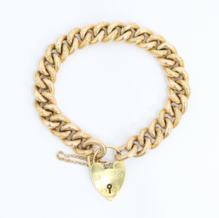 A 9ct yellow gold patterned curb link bracelet with a 18ct gold heart padlock. £1,650.00