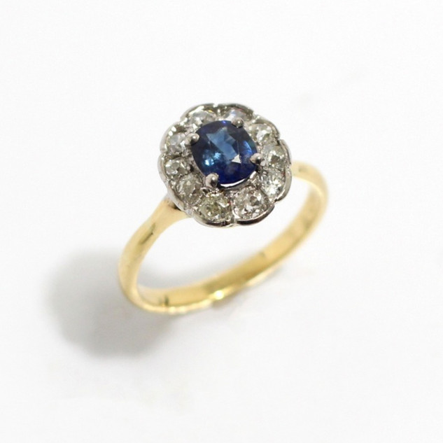 18ct yellow gold and platinum sapphire and diamond cluster ring. Comprising of a central oval sapphire with old cut diamond surround. Total diamond weight 0.75ct. £1,200.00