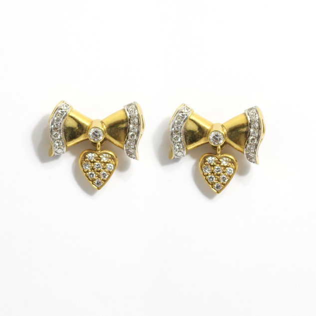 18ct yellow gold bow earrings with diamond edges and a diamond set drop feature below. £1,250.00