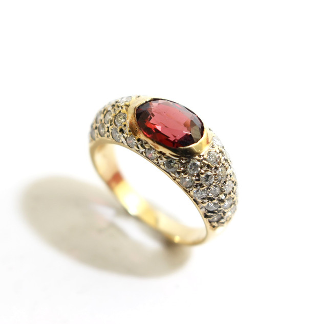 18ct yellow gold mounted sapphire dress ring. Comprising of a central oval red/ brown sapphire within a pave diamond set design. Circa 1970. £1,650.00
