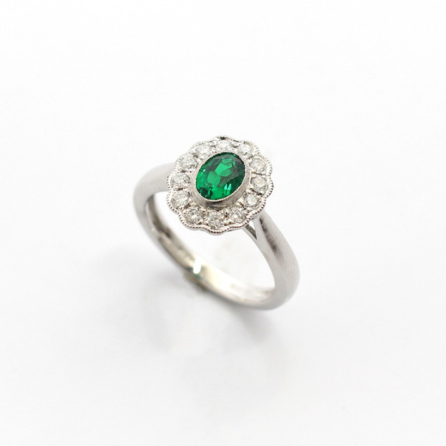 Platinum emerald and diamond oval cluster ring. The central oval emerald of fine colour, with good clarity 0.44ct. Completed with outer border of circular modern brilliant cut diamonds, 0.33ct in total, with a fine millgrain setting. £2,500.00