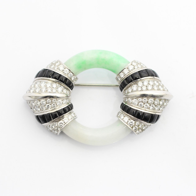 A platinum, jade, onyx and diamond brooch. The jade circlet from green to white. Completed with platinum, diamond and calibre cut onyx panels. £12,000.00