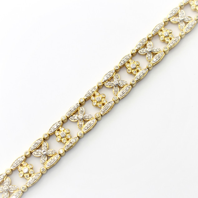 18ct yellow gold diamond panel bracelet. Comprising of diamond set cluster links alternating with diamond set fancy links with borders of diamonds to each side. Total diamond weight estimated 4.50cts. Italian circa 1990.