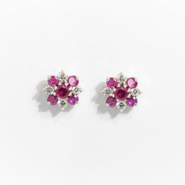 18ct white gold ruby and  diamond fancy cluster earrings. Comprising of five circular pinkish coloured rubies with four circular diamonds. Total ruby weight 0.77ct, total diamond weight 0.33ct. £3,250.00