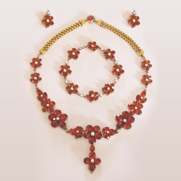 An unusual antique suite of jewellery set with hessonite garnets and half pearls mounted in 15ct gold. The double chain section has been bloomed to give a much yellower appearance, a practice often used in the 19th century. Also known as cinnamon stone, hessonite garnet is mainly found in Sri Lanka, but is also mined in Brazil, India, Canada, Madagascar, Tanzania and the United States.
