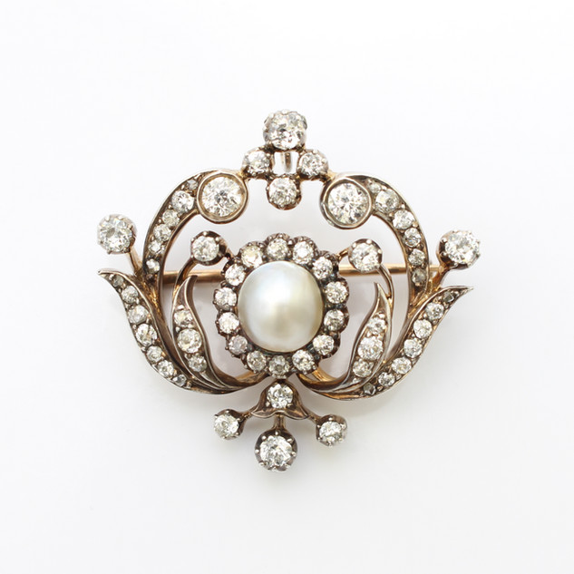 Gold mounted and platinum fronted Edwardian pearl and diamond pendant. Comprising of a central oval natural salt water pearl within a diamond cluster feature. Completed with outer borders of diamonds in an Art Nouveau design.  £6,000.00