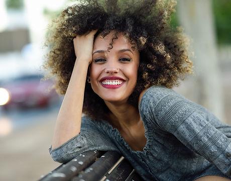 Mulher de sorriso com cabelo encaracolado