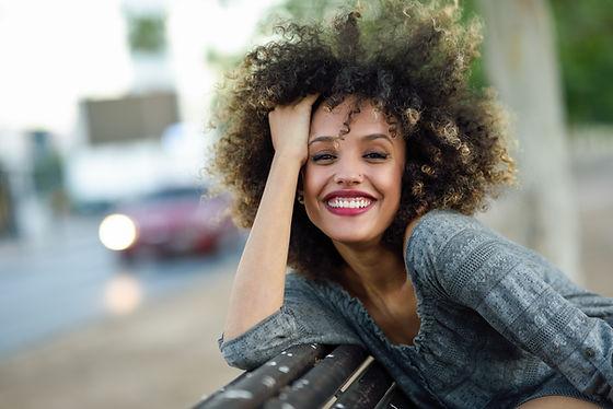 Lachende vrouw met krullend haar