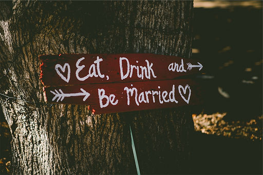 Wooden Weding sign white painted writing nailed to a tree trunk eat drink and be married