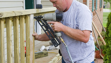 Carpenter is adding rails to porch on fr