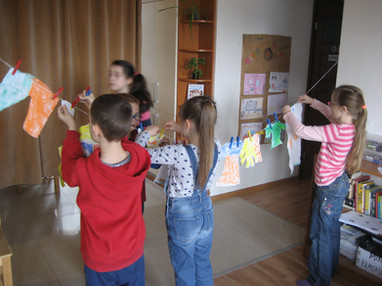 Kids hanging paper clothes