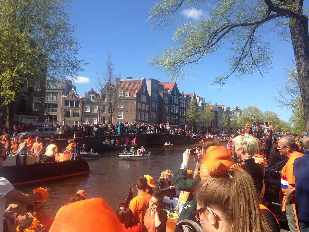 Party boats full of people wearing orange moving down a canal lined with celebrators and historic houses