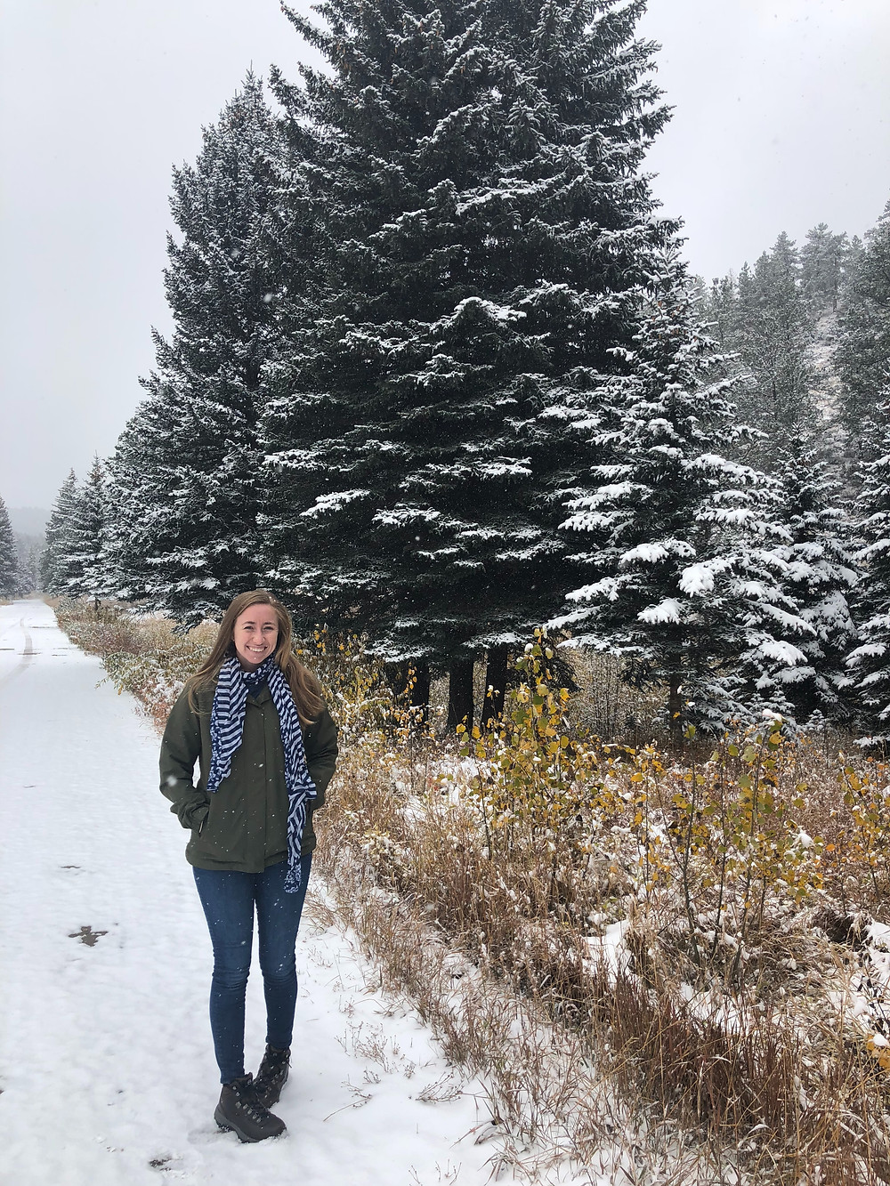 Young lady standing on snow covered trail with pine trees behind her.