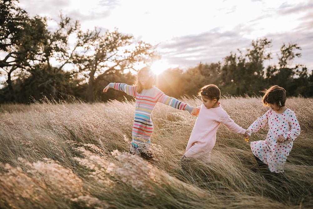 Three young girls walking through a field of tall golden grass.