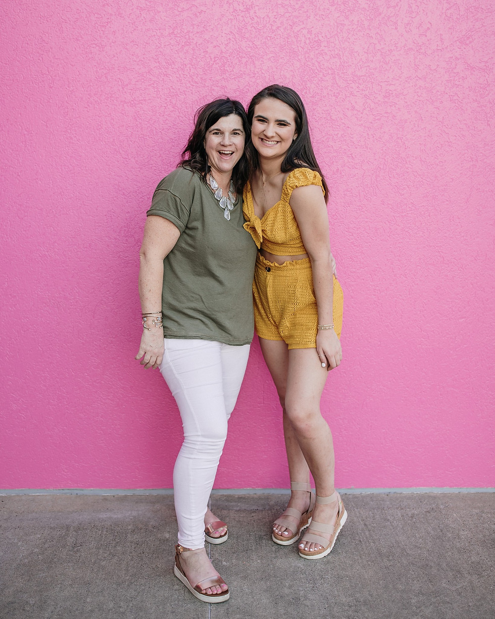Mom and daughter in front of bright pink wall