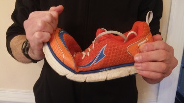 Demonstration of running shoe flexing at ball of foot.
