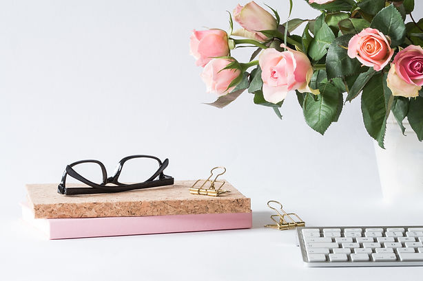 eyeglasses-on-book-beside-rose-and-keybo