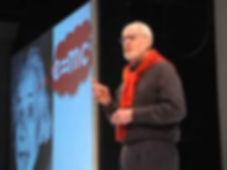 Picture of John Danner speaking on stage with Albert Einstein slide
