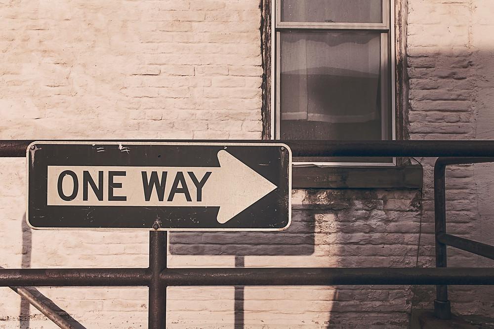 One Way Street Sign on Railing