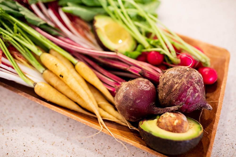 Wooden serving dish full of ellow barrots, red beets, an avocado cut in half, and pink radishes