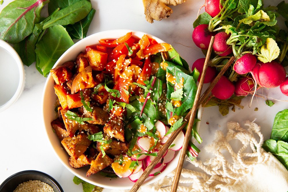 Bowl of tempeh, sweet potatoes, red bell pepper, green, radish, with sauce and chop sticks. Greens, ginger, and radishes are in the background of the picture