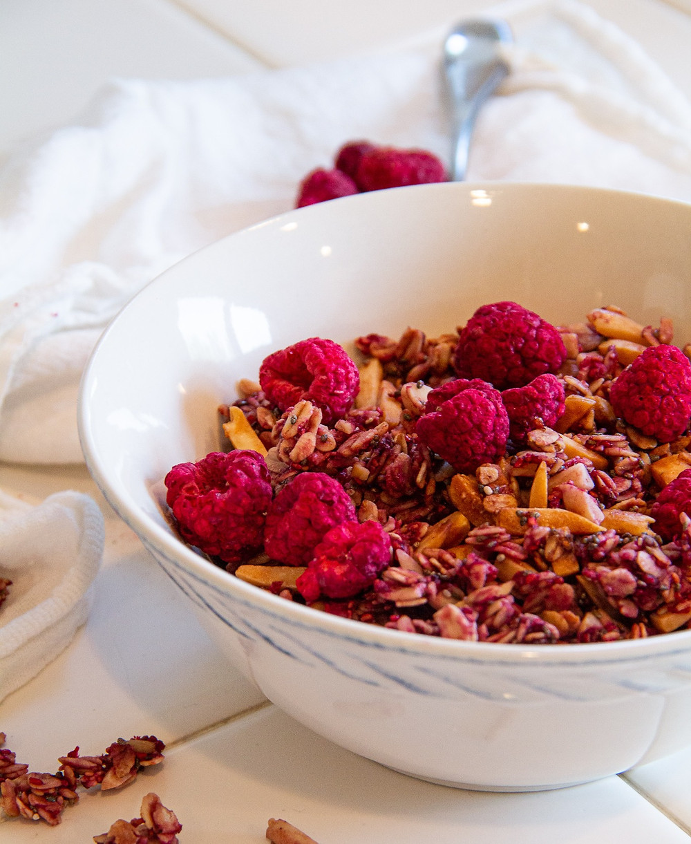 Bowl of raspberry almond granola with dried raspberries on top.