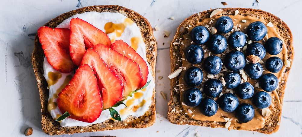 Two pieces of toast. One with yogurt, strawberries, and honey. The second piece of toast with peanut butter and blueberries.