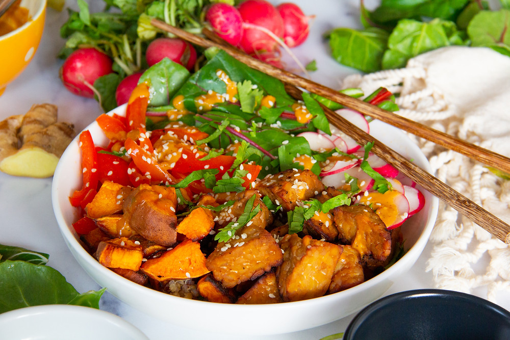 Bowl of tempeh with vegetables, sesame seeds, cilantro, and spicy peanut ginger sauce