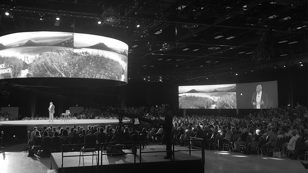 A large conference with the audience looking at the speaker and screen on stage.