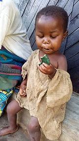 Malnourished child receiving spirulina cookie at POPOF spirulina centre
