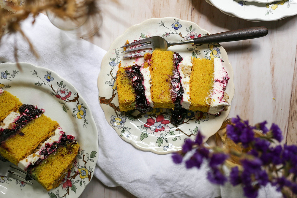 Slice of cake with layers of blueberry compote, vanilla frosting and yellow turmeric spice cake.