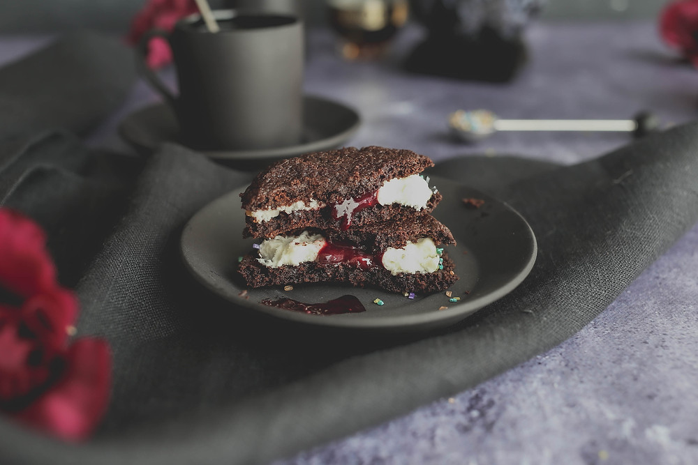 Chocolate cookie sandwich split in half with blackberry jam pouring from it.
