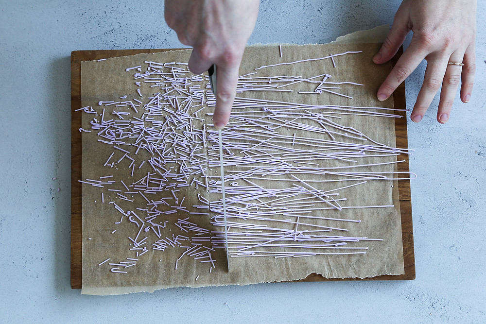 A cutting board with skinny sticks of dried frosting being cut into small sticks