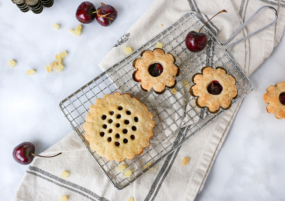 Two small cherry pies in various sizes, with decorative circle cut outs on the top layer of crust. Pies are spread out on a napkin with scattered cherries and candied ginger.
