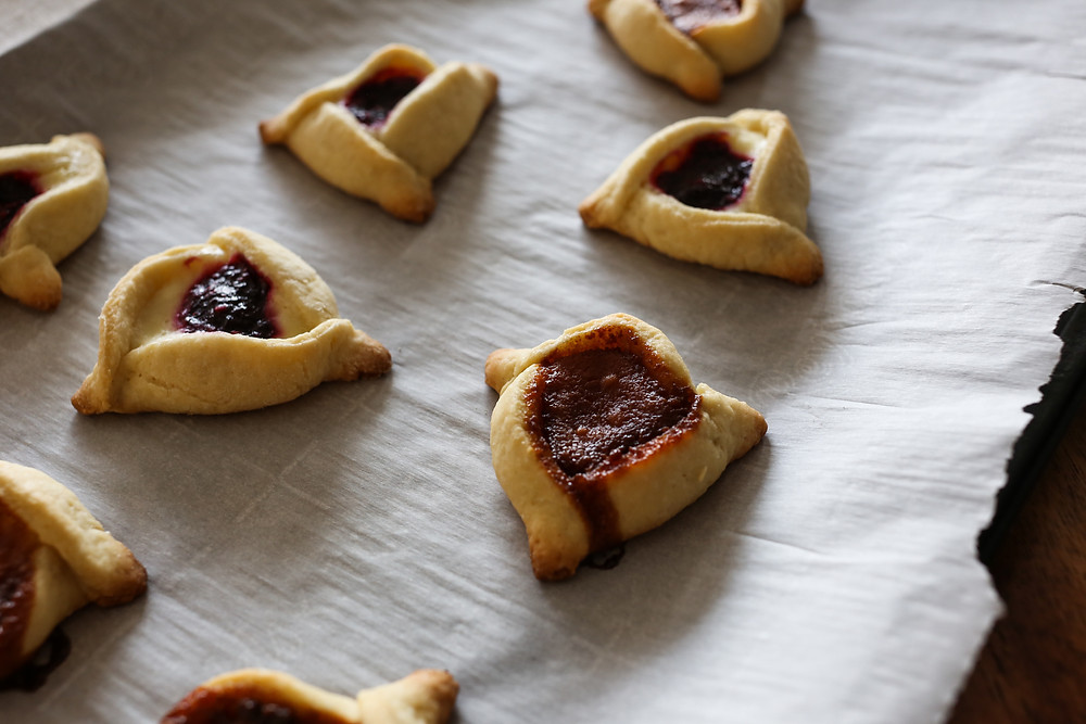Jewish Hamantaschen cookies filled with cheesecake and a jelly or caramel filling