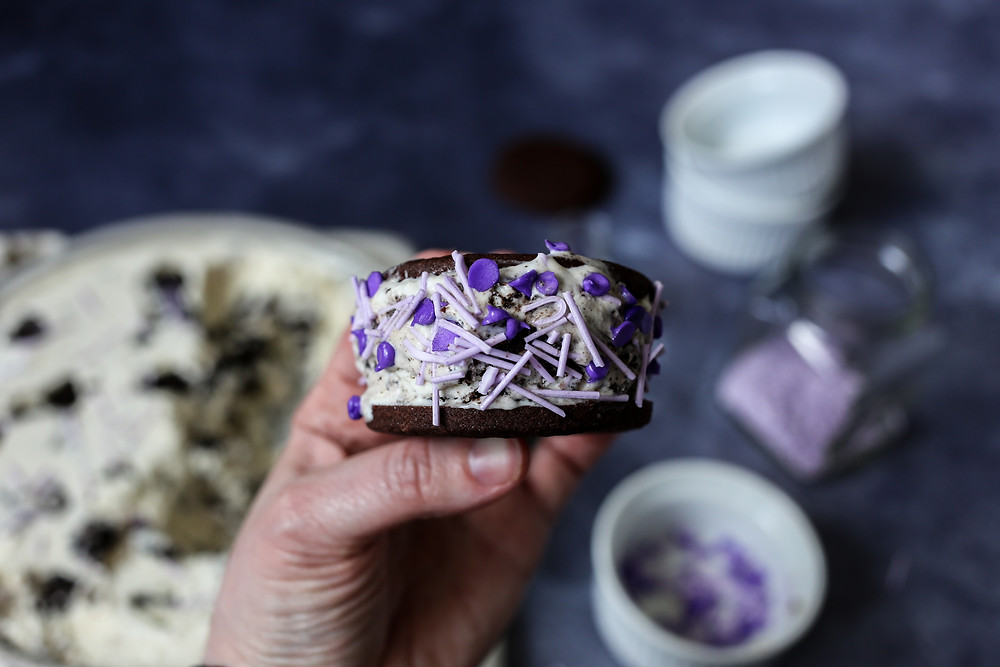 A hand holding an homemade ice cream sandwich with lavender oreo ice cream sandwiched between two chocolate cookies, covered in purple sprinkles.