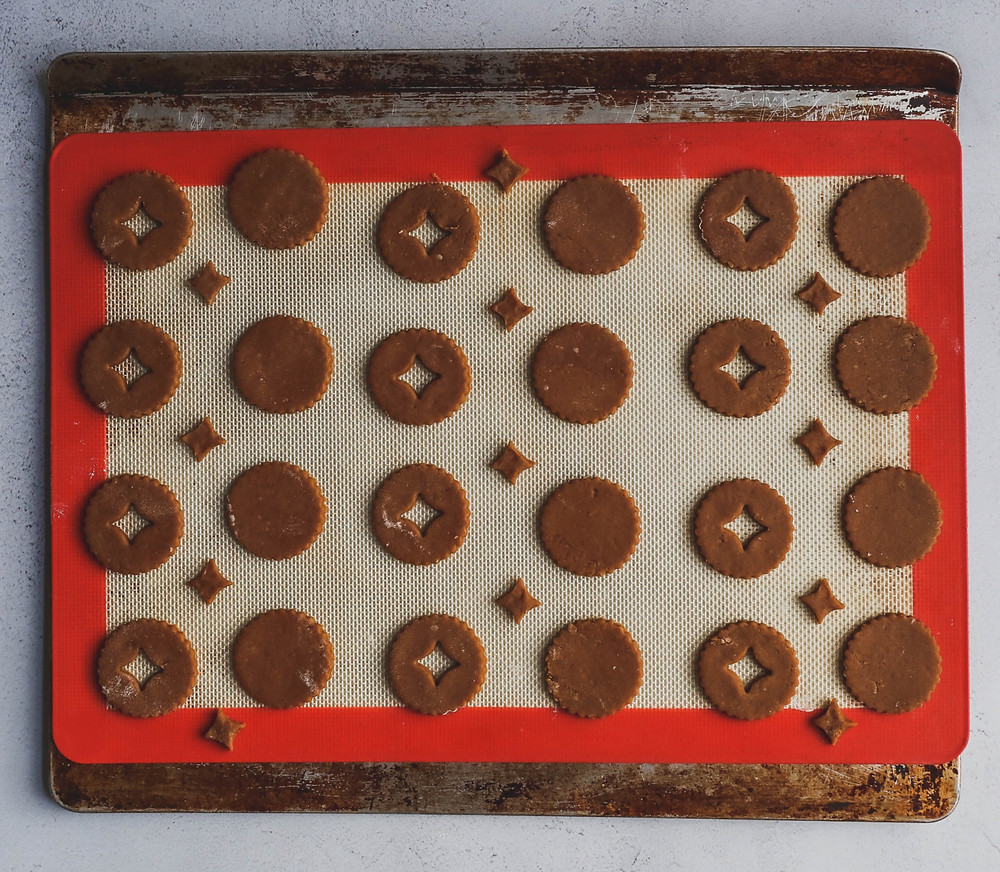 Cut out gingerbread cookies on a baking sheet.