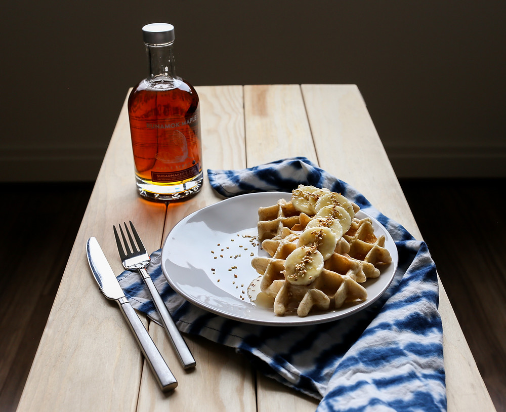 Sesame waffles topped with bananas and sesame seeds. Waffles are on a white plate on top of a tie dye napkin, with a bottle of Runamok Maple on the side.