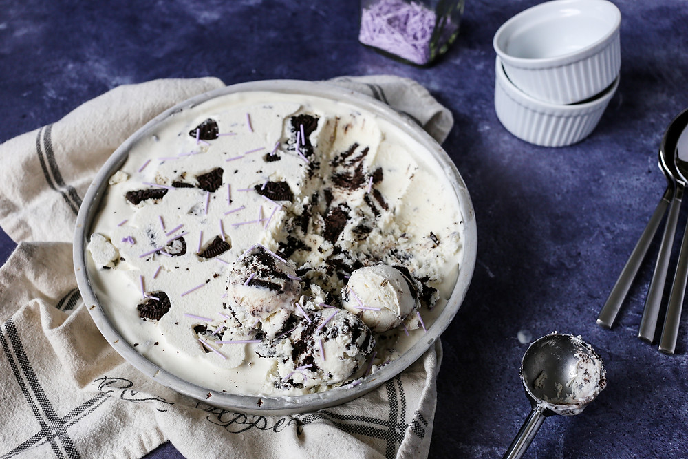 Homemade Lavender Oreo Ice Cream in a pie dish with several scoops taken out.