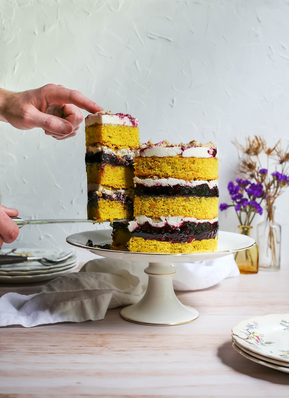 A person carefully removing a large slice of cake, exposing more of the layers.