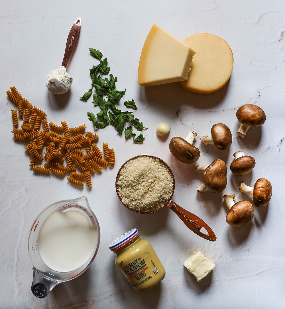 ingredients on a table: pasta, parsley, mushrooms, cheese, mustard and butter