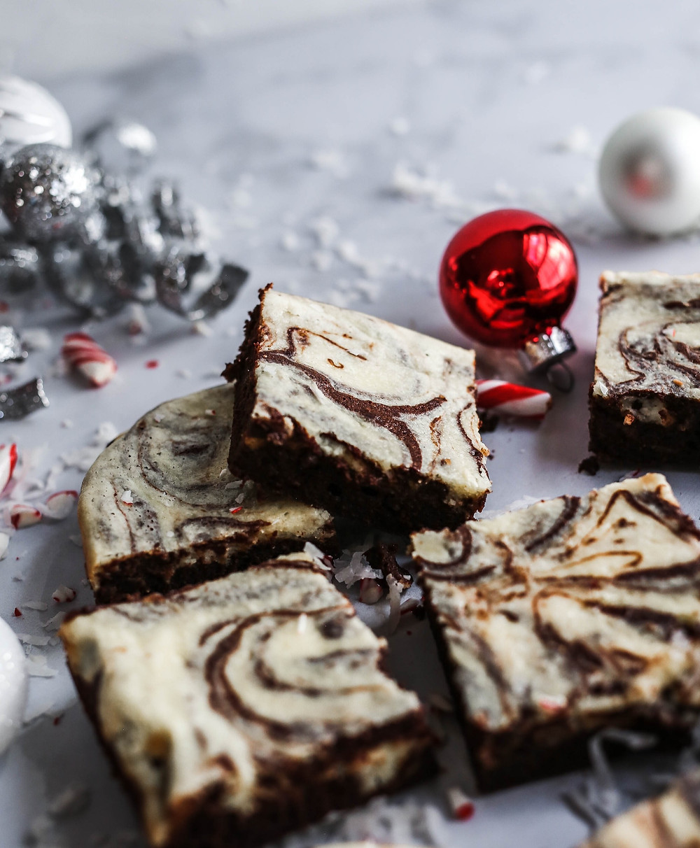 Chocolate brownies swirled with peppermint cheesecake surrounded by coconut flakes, Christmas ornaments and crushed candy canes