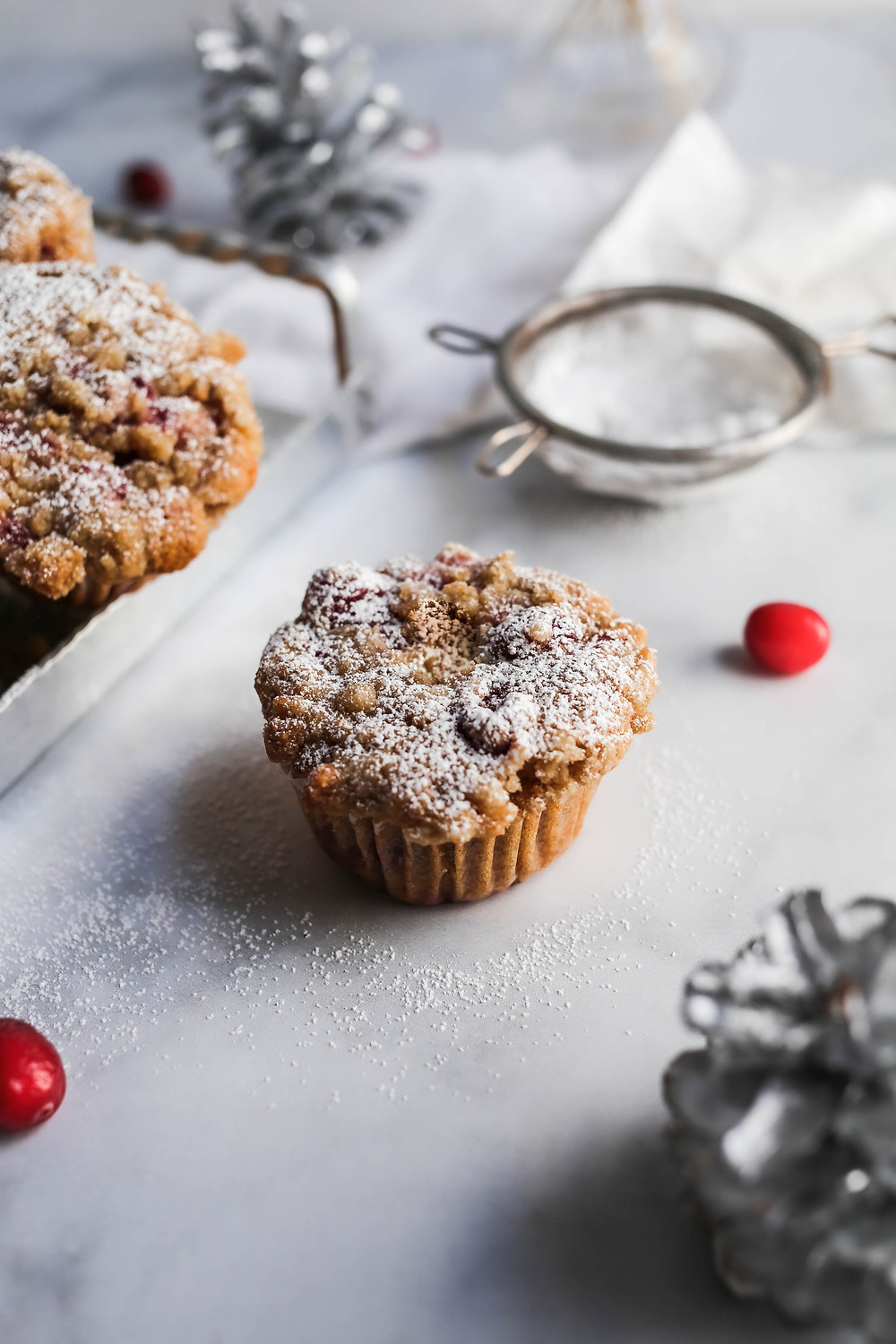 A single cranberry muffin surrounded by silver pinecones and powdered sugar