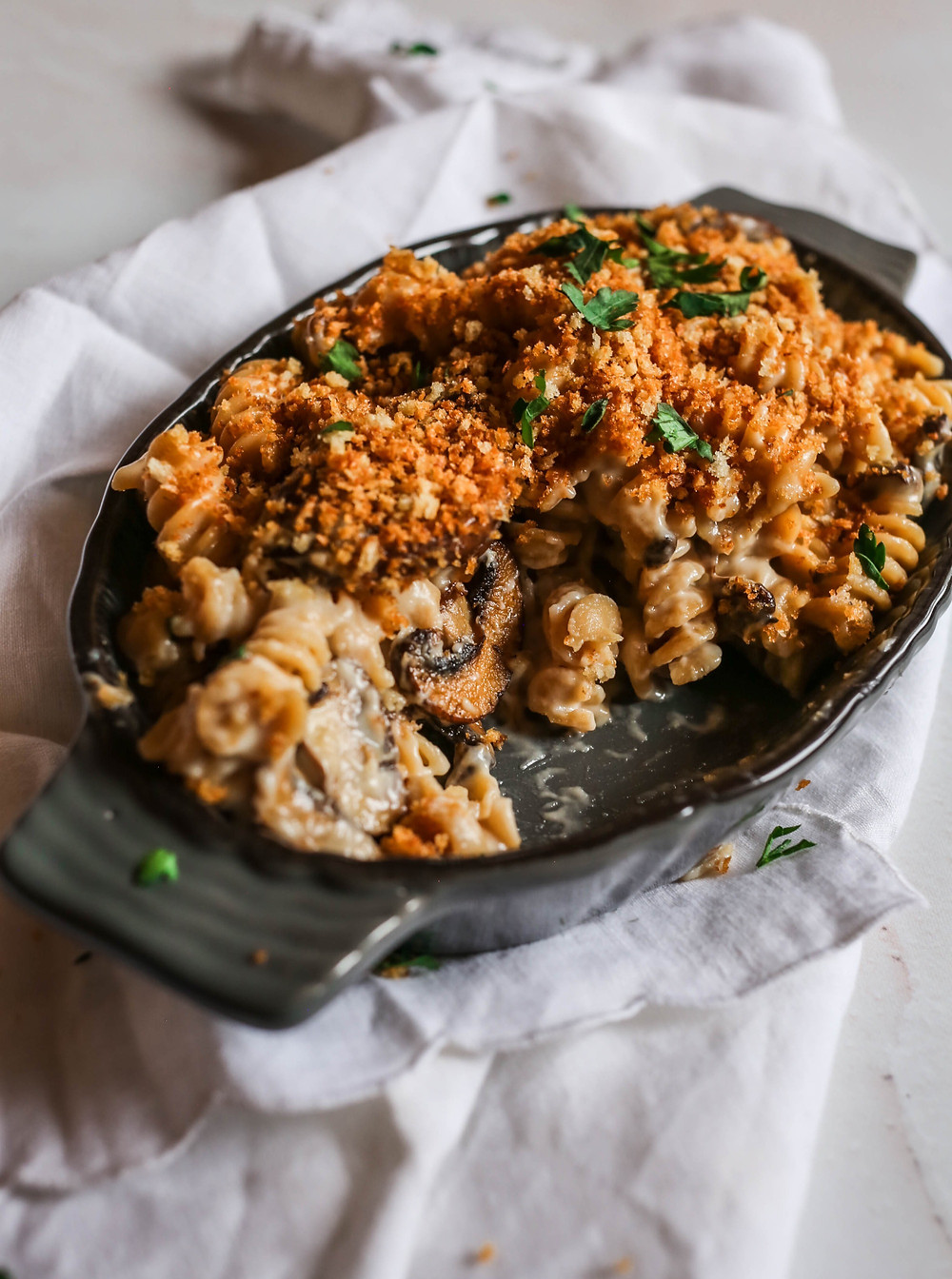 Rotini mac and cheese mixed with mushrooms and topped with garlicky toasted panko bread crumbs.