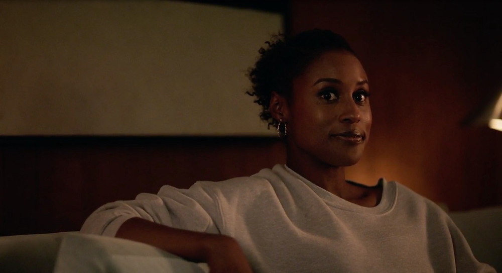 Issa Dee sits on her couch in the Season finale.