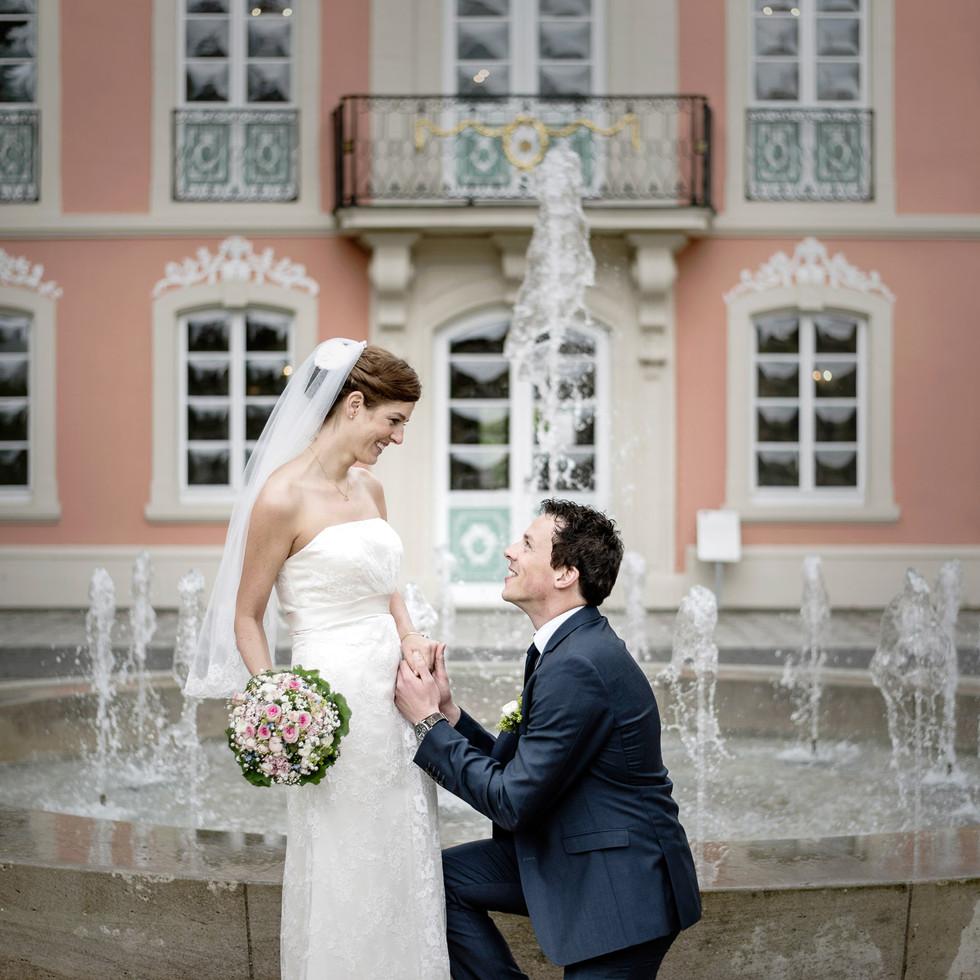 Bräutigam kniet vor Braut vor Schloss